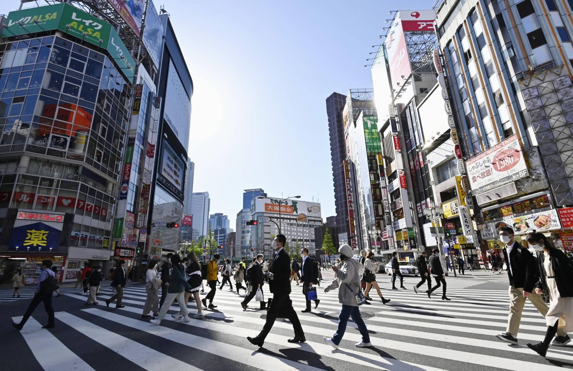 People walk in Tokyo's Shinjuku district on Monday